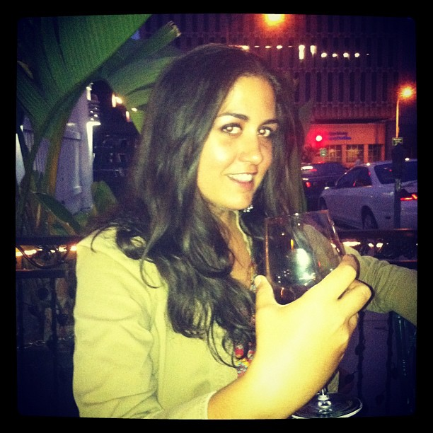 dark-haired woman drinking a glass of wine