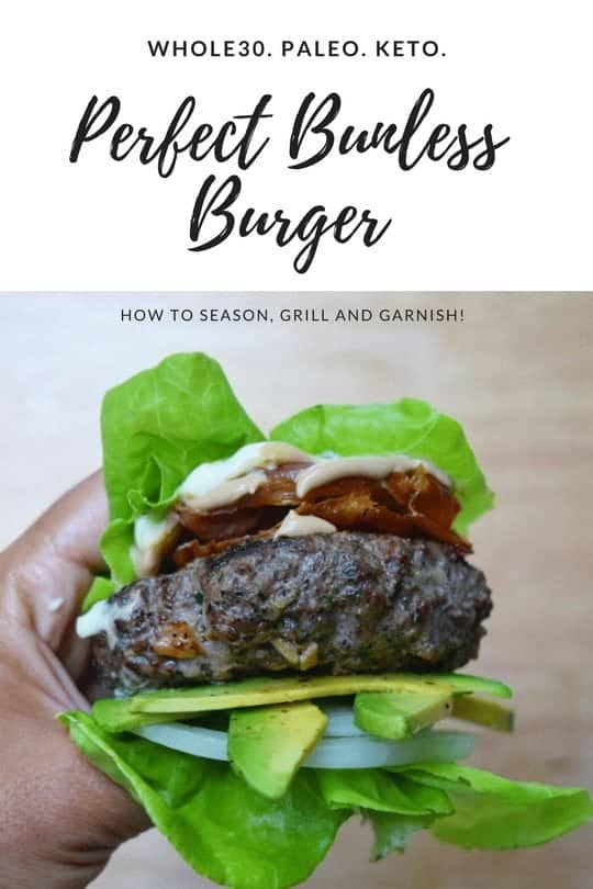 hand holding a bunless burger with avocado, lettuce, and onion