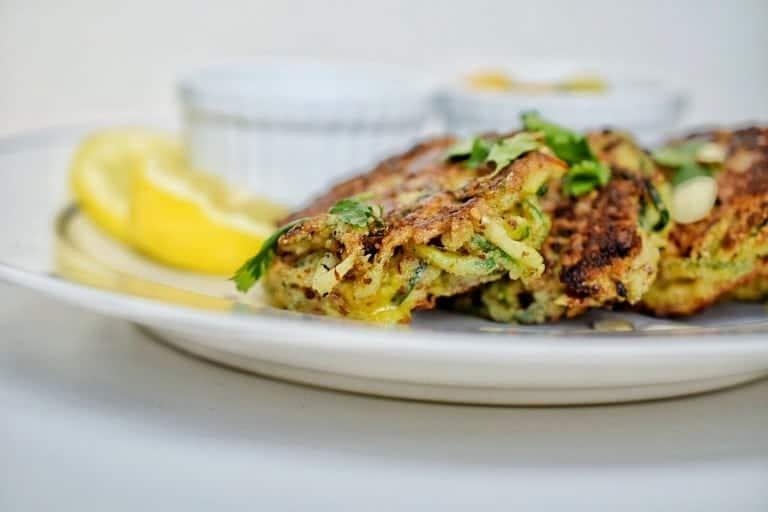 closeup of zucchini fritters with lemon in the background