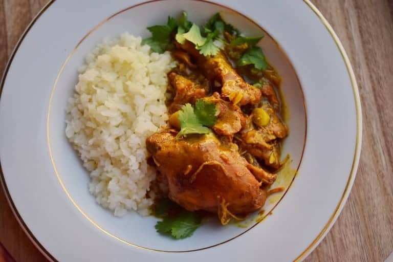 indian butter chicken and rice on a white plate