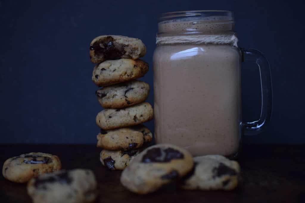 stack of chocolate chip cookies next to a glass of chocolate milk
