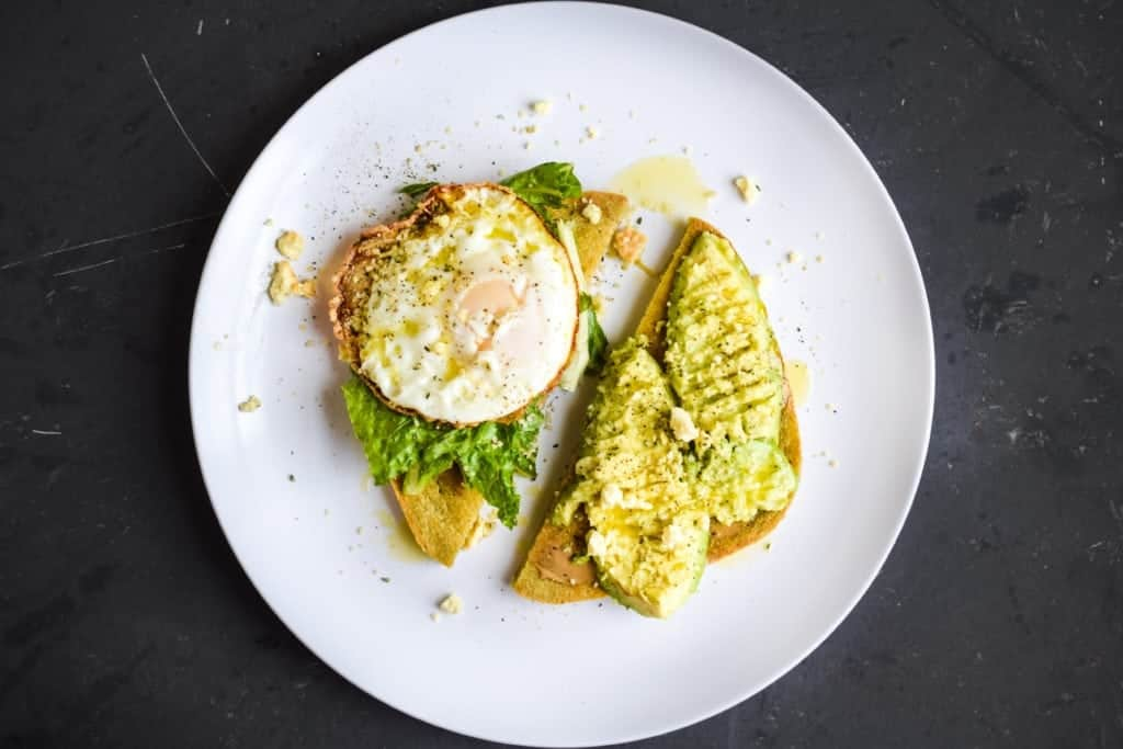 black background with avocado toast and egg