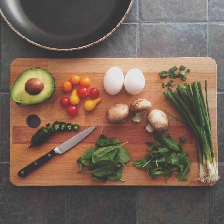 cutting board with avocado, tomato, eggs, spinach, mushrooms, and green onions