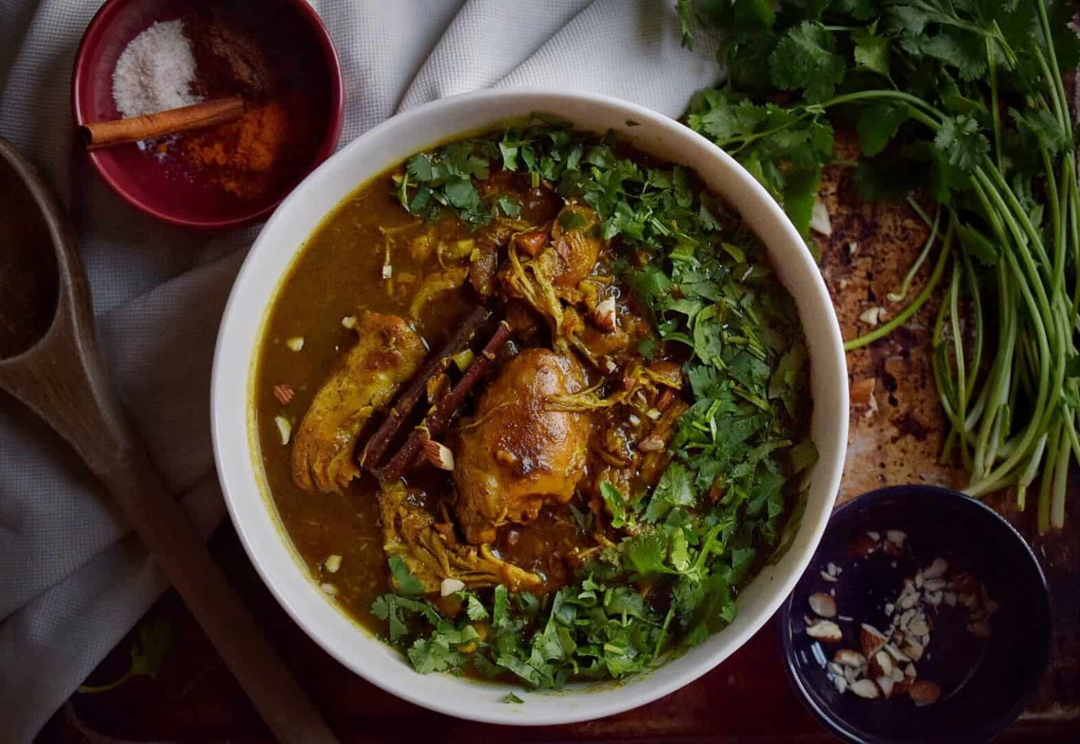 indian butter chicken in a white bowl surrounded by spices and cilantro