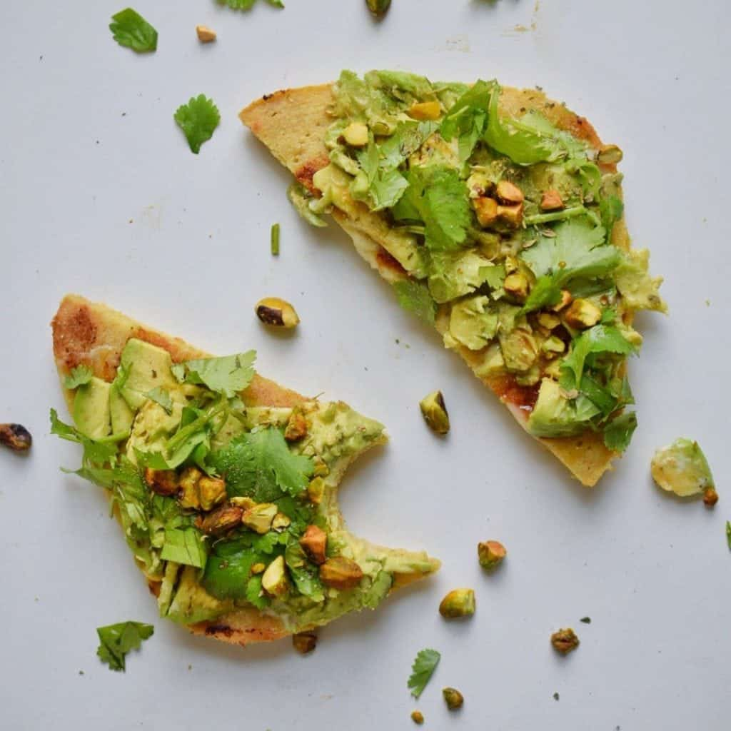 bread on white plate with avocado and herbs