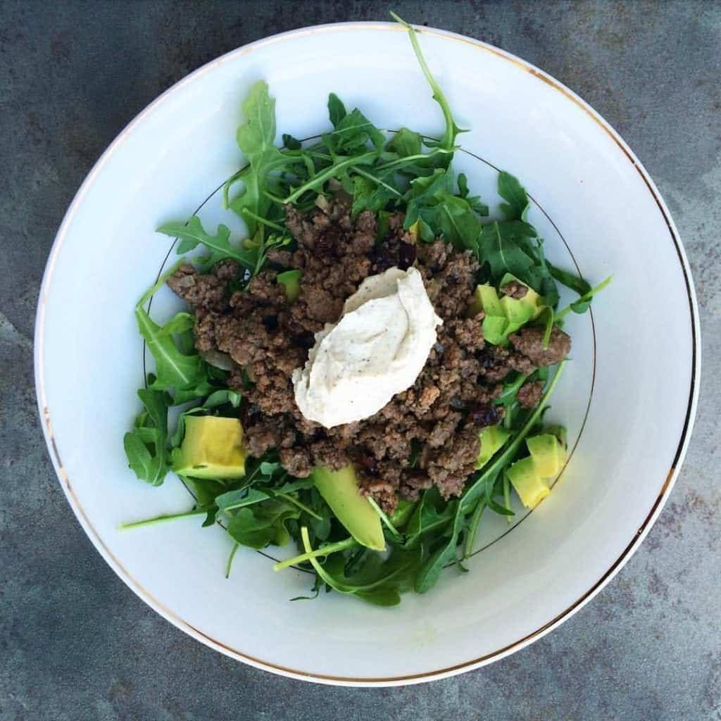 bowl of greens topped with meat and cashew sour cream