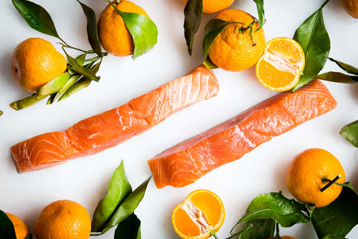 Overhead shot of beautifully coral wild caught salmon fillets on a white background, surrounded by fresh oranges with the leaves and stems intact.