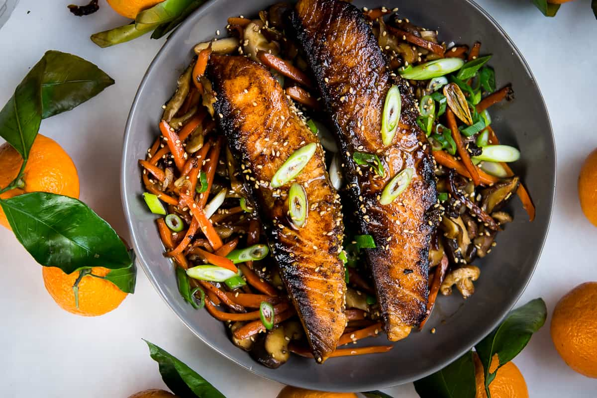 An overhead shot of Orange Ginger Salmon fillets, cooked till caramelized and almost blackened on the edges on a bed of veggies from the same recipe, garnished with green onions cut on a bias, served in a light charcoal colored bowl. The bowl sits on a white background, surrounded by fresh whole oranges with the steams and leaves intact.