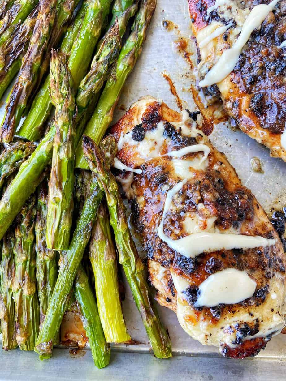 Macadamia Nut Garlic Chicken, seared to perfection, sits on an aluminum baking sheet lined with parchment paper. The chicken is drizzled with macadamia nut butter and served alongside broiled asparagus.