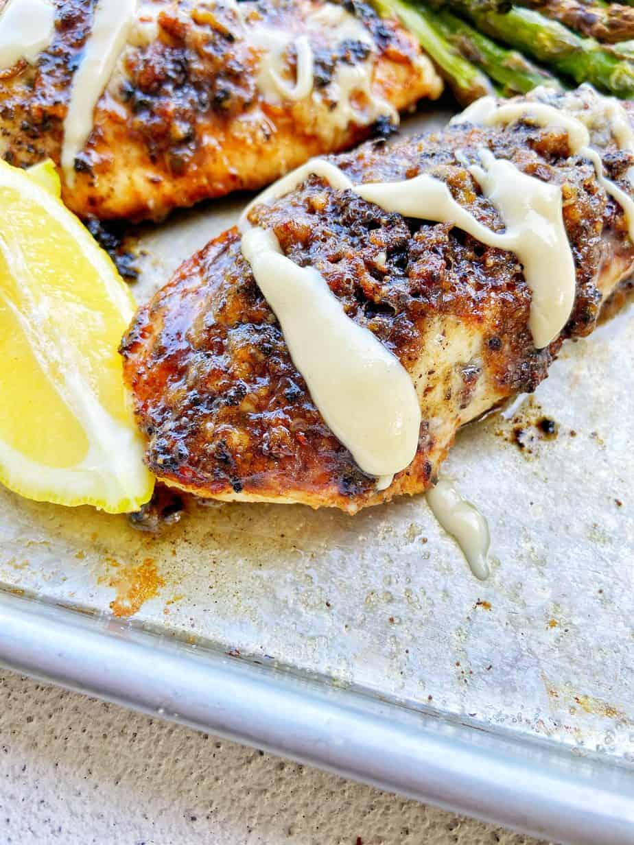 Macadamia Nut Garlic Chicken, seared to perfection, sits on an aluminum baking sheet lined with parchment paper. The chicken is drizzled with macadamia nut butter and garnished with lemon wedges and broiled asparagus sits in the background.