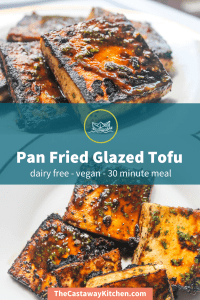 "Two photos of several square blocks of pan fried glazed tofu sitting on a white plate. The tofu is blackened and caramelized in some areas, with herbs and seasonings. Across the middle of the photo is a transparent dark teal banner with ""Pan Fried Glazed Tofu"" and ""dairy free - vegan - 30 minute meal"" on a second line of text."