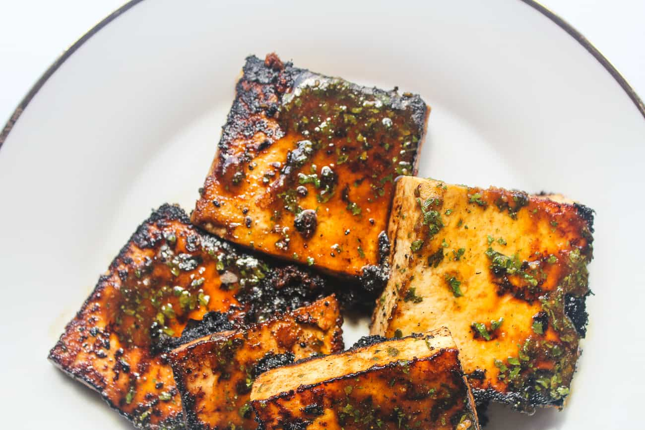Overhead shot of several square blocks of pan fried glazed tofu sit on a white plate. The tofu is blackened and caramelized in some areas, with herbs and seasonings.