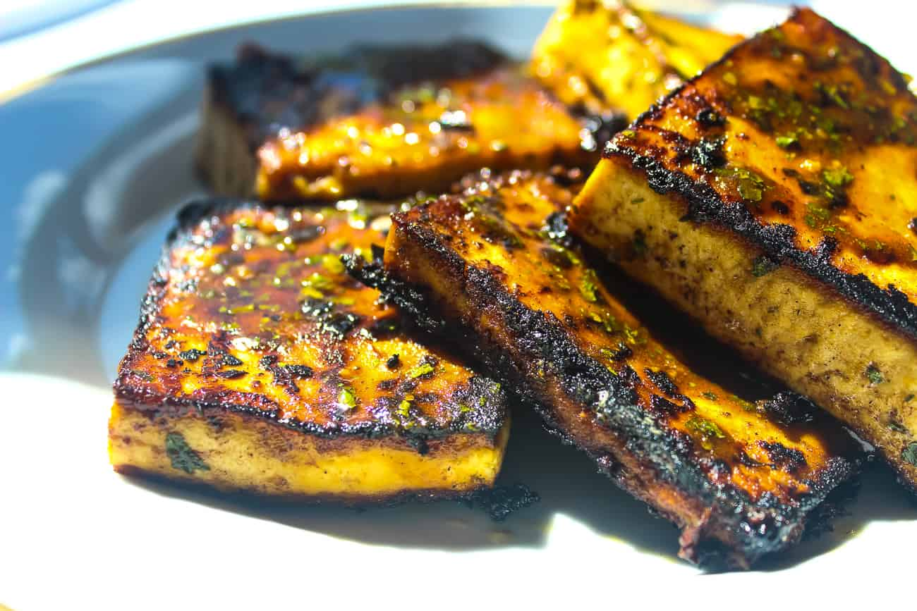 Several square blocks of pan fried glazed tofu sit on a white plate. The tofu is blackened and caramelized in some areas, with herbs and seasonings.