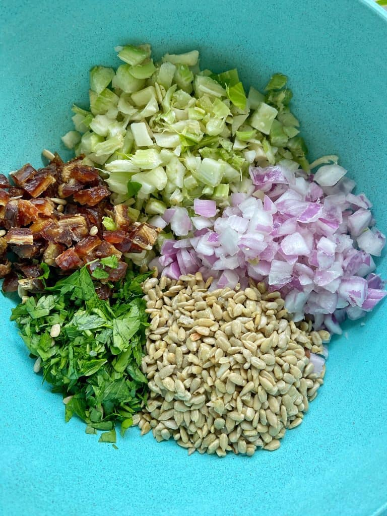 Ingredients for shredded chicken salad sit in a teal bowl: finely diced celery and red onion, minced fresh parsley, chopped pitted dates, and raw sunflower seeds.