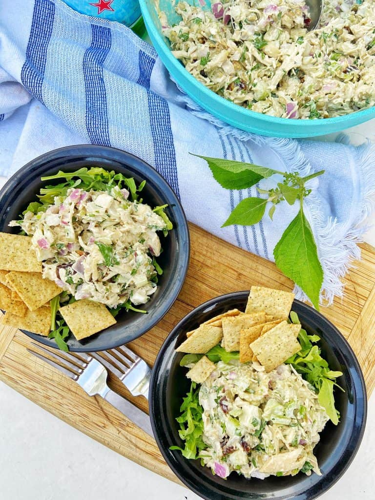 Two black bowls with a shredded chicken salad sitting on top of a bed of arugula, garnished with crackers. The bowls sit on a wooden cutting board with two forks, a gray and white striped cloth napkin, and a large bowl of shredded chicken salad to the side.