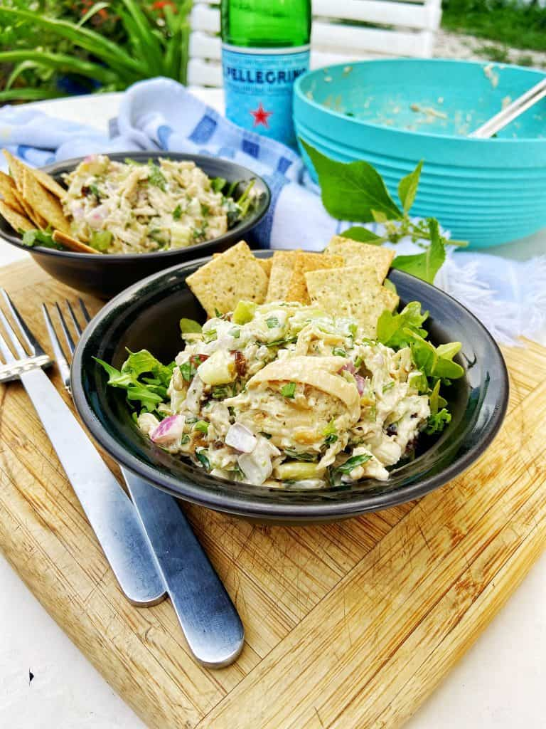 Two black bowls with a shredded chicken salad sitting on top of a bed of arugula, garnished with crackers. The bowls sit on a wooden cutting board with two forks, a gray and white striped cloth napkin, and a large bowl of shredded chicken salad in a large teal bowl on the side.