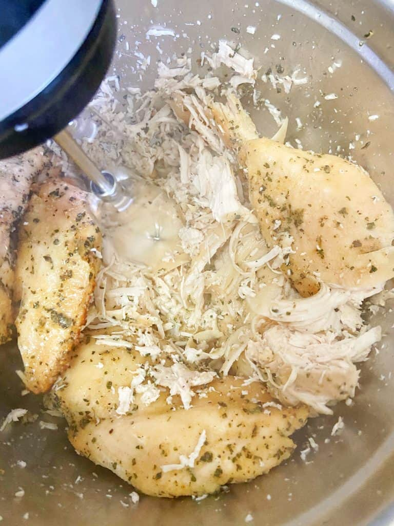 Freshly cooked (and steaming) seasoned chicken breasts sit in a large metal bowl. The chicken is being shredded with a hand mixer.