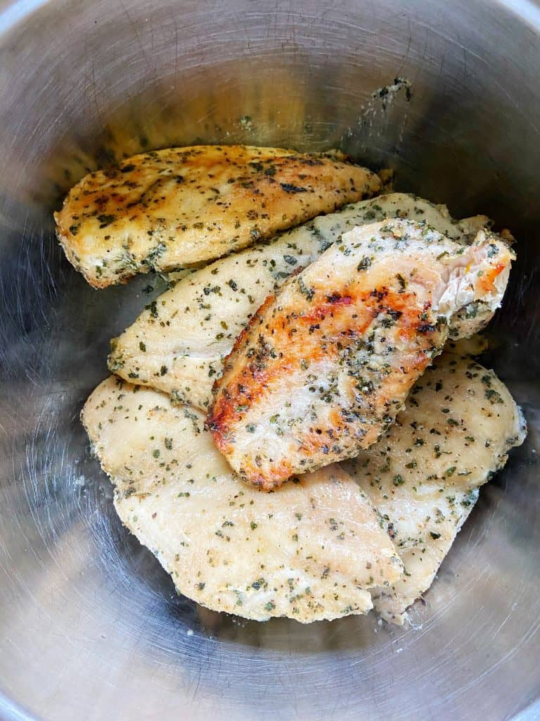 Freshly cooked, slightly caramelized seasoned chicken breasts sit in a large metal bowl.