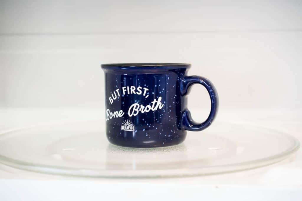 A dark blue coffee mug full of AIP Brownie Mug Cake batter in the microwave.