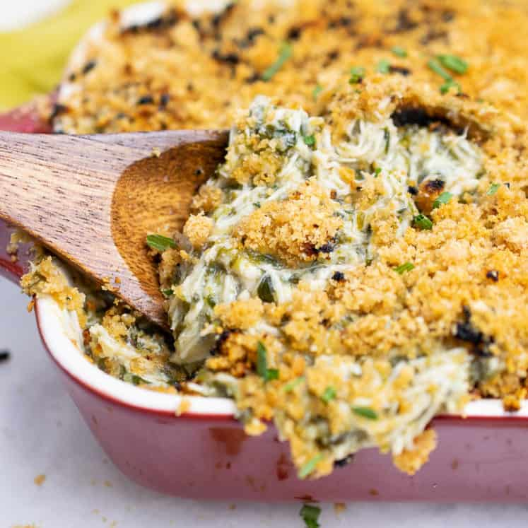 Scooping a wooden spoon into cheesy dairy-free AIP Chicken Casserole with spinach, baked and bubbly in a red casserole dish, topped with crunchy pork panko.