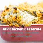 Cheesy dairy-free AIP Chicken Casserole with spinach, baked and bubbly in a red casserole dish, topped with crunchy pork panko.